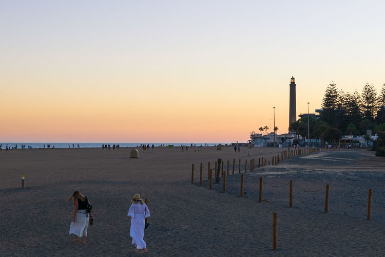 Rear view of people walking on beach against clear sky during sunset