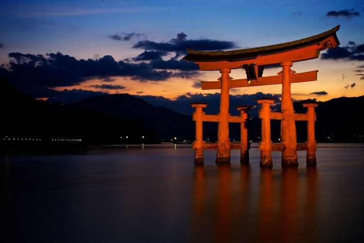 Torii Gate In Lake Against Sky During Sunset