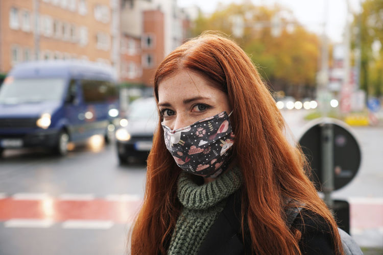 Young woman with cloth face mask on busy street with car traffic
