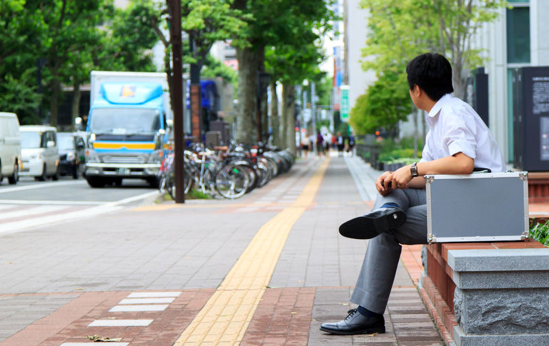 Businessman Sitting With Briefcase On Surrounding Wall In City