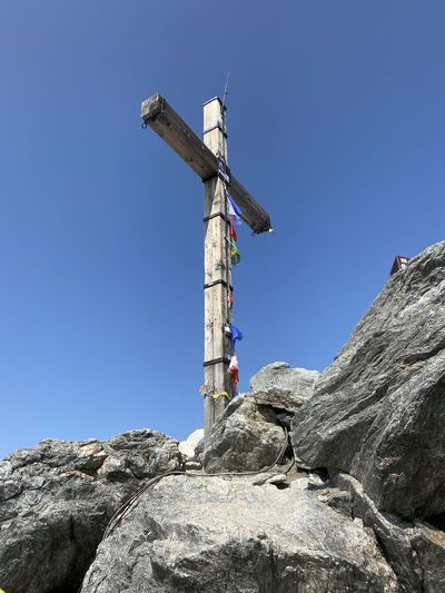 Low angle view of cross on rock against clear blue sky