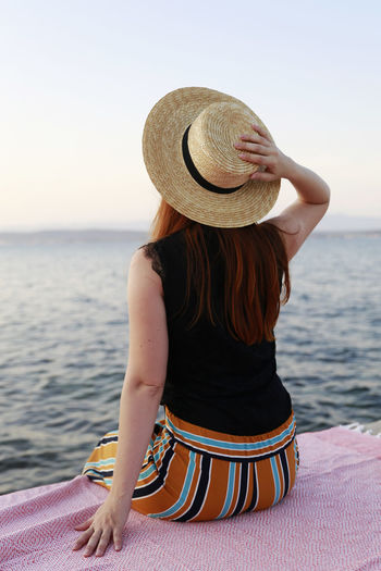 Rear view of woman with hat on beach