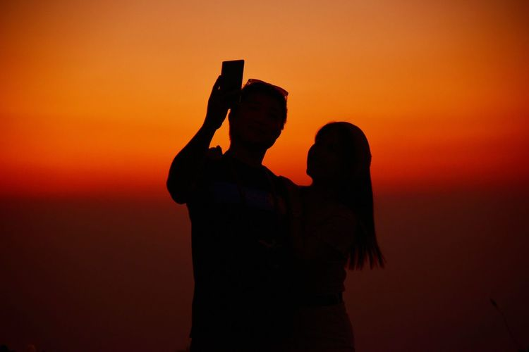 Silhouette of woman photographing orange sunset sky