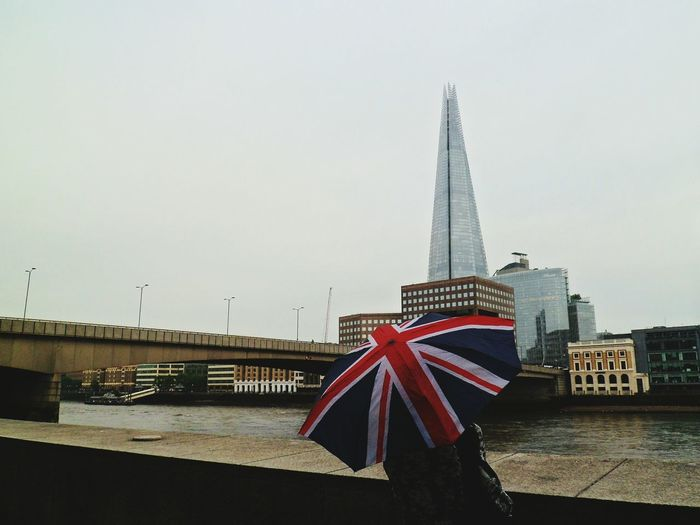 Rear View Of Woman With British Flag Umbrella Against Shard London Bridge In City