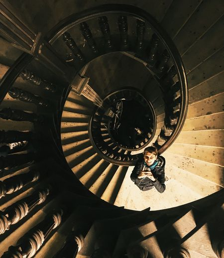 Directly Above View Of Woman Standing On Spiral Staircase