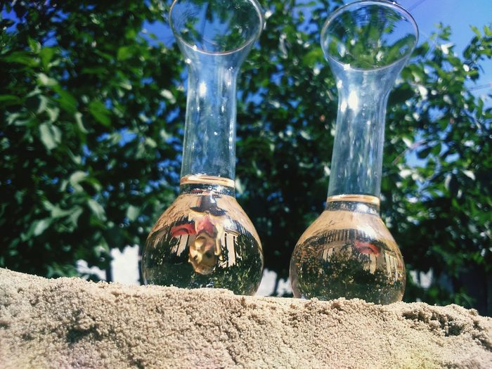 Low angle view of elderberry syrup in glass containers on sand