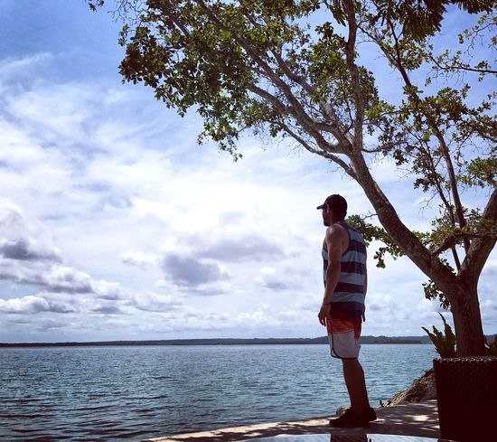 EyeEmNewHere One Person Cloud - Sky Rear View Tree Water Standing Sky Outdoors Nature Landscape