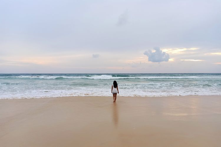 Rear view of woman walking at beach against cloudy sky during sunset