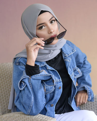 Fashionable Young Woman Wearing Hijab Against Wall