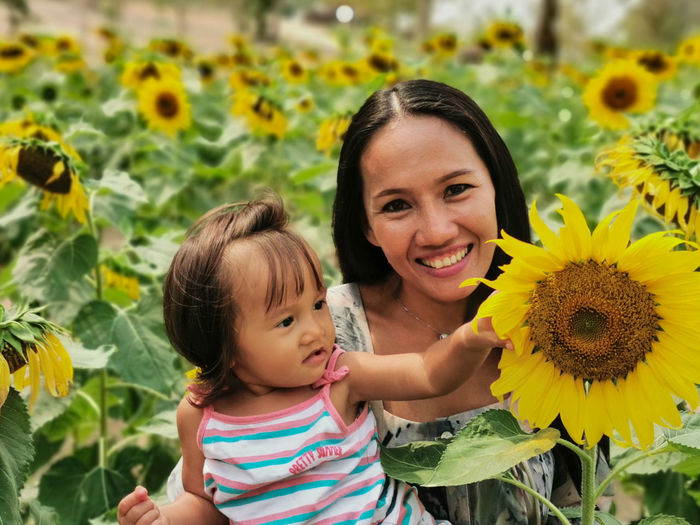 Portrait of mother and daughter on sunflower