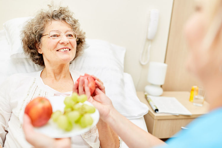 Nurse giving fruits to patient lying on bed in hospital