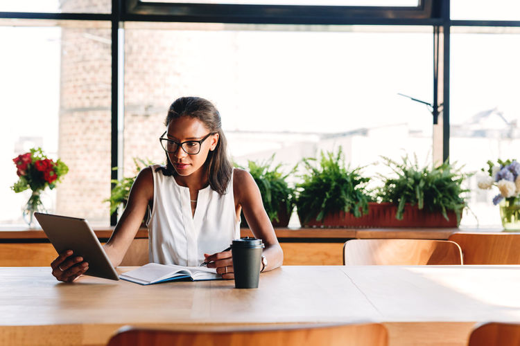 Young Business person Owner Indoors  Cafe Sitting Taking Notes Real People Wireless Technology One Person Coffee Shop Digital Tablet Writing Looking African American Working Window