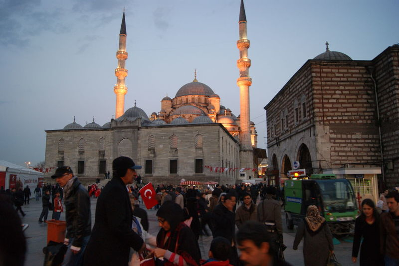 Crowd outside yeni cami mosque against sky at dusk