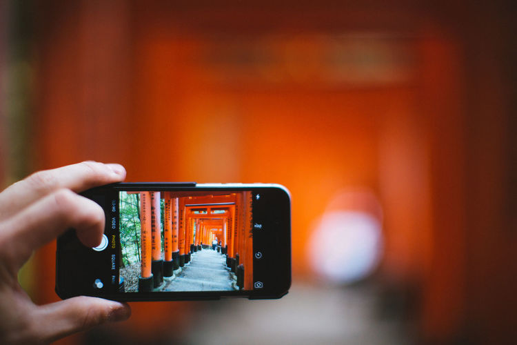 Temple Human Hand Technology Hand Human Body Part Holding Wireless Technology One Person Photography Themes Smart Phone Communication Portable Information Device Close-up Arts Culture And Entertainment Finger