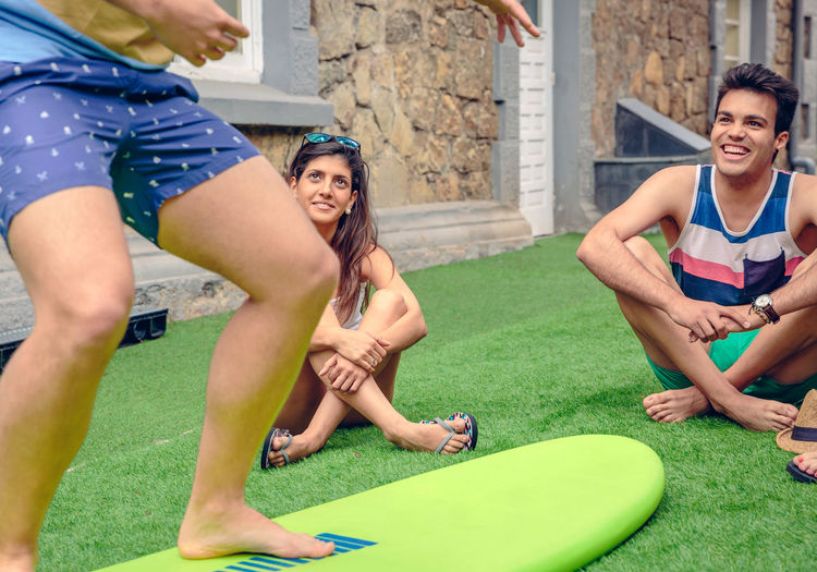 Young friends by surfboard at turf