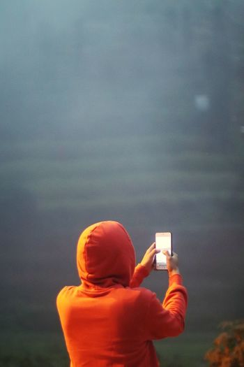 Rear view of man photographing with mobile phone