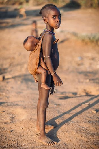Hamer girl and baby in Turmi - Ethiopia Baby Tribe Omo Valley Tribal Ethiopian Ethiopian Photography 🇪🇹 Portrait Of A Woman Portrait Photography Africa African Travel Ethiopia Travel Destinations Childhood Offspring Child One Person Full Length Clothing Girls Sunlight Nature Land Walking Females Cute Emotion Standing Outdoors Lifestyles