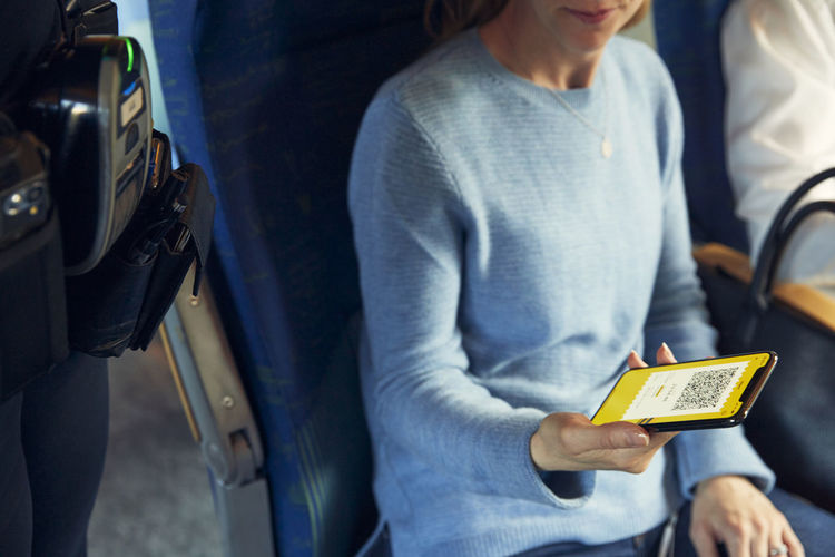 Midsection of man using mobile phone while sitting in bus