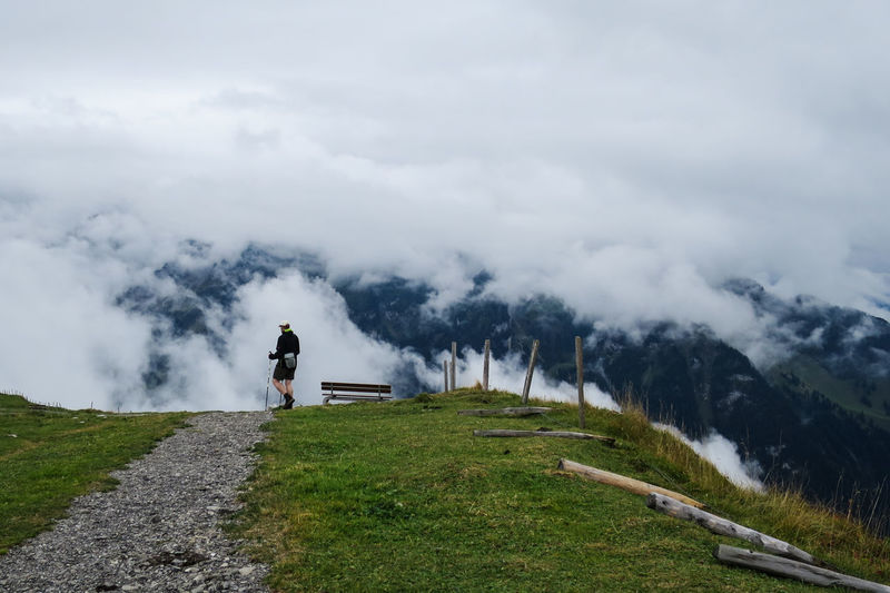 Man and woman walking on mountain against sky