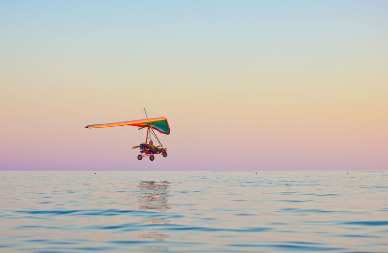 Hang glider over sea against clear sky at dusk
