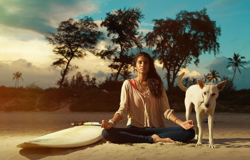 Portrait Of Young Woman With Dog Meditating While Sitting At Beach Against Sky During Sunset