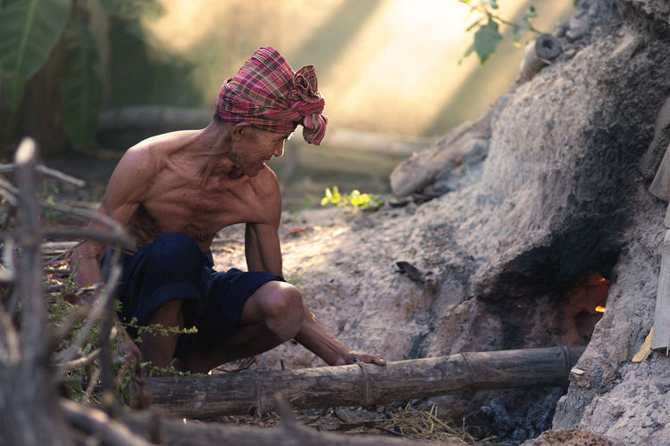 Senior Man Burning Bamboo In Forest