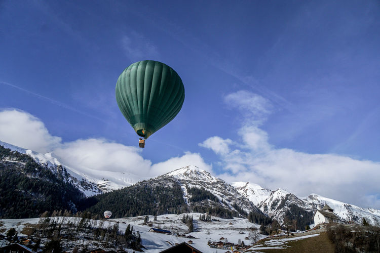 Scenic view of hot air ballon in front of snowcapped mountains against sky