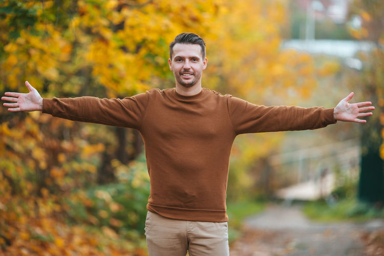 Portrait of man with arms raised standing during autumn