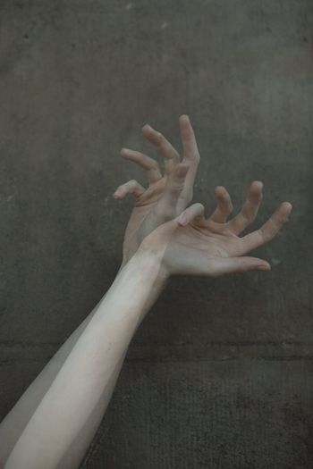 Cropped hands of woman gesturing against wall