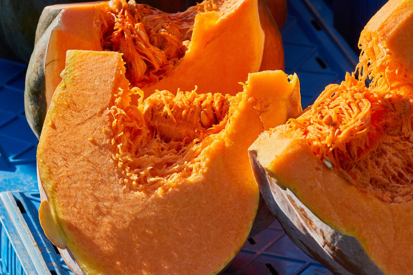 Sliced pumpkin with colorful orange fruit pulp inviting for taste on a local market. Colorful Eatng First Eyeem Photo Freshness Green Color Healthy Local Landmark Low Carb Nature Nature_collection Orange Color Pumpkin RGanimals Vegetable
