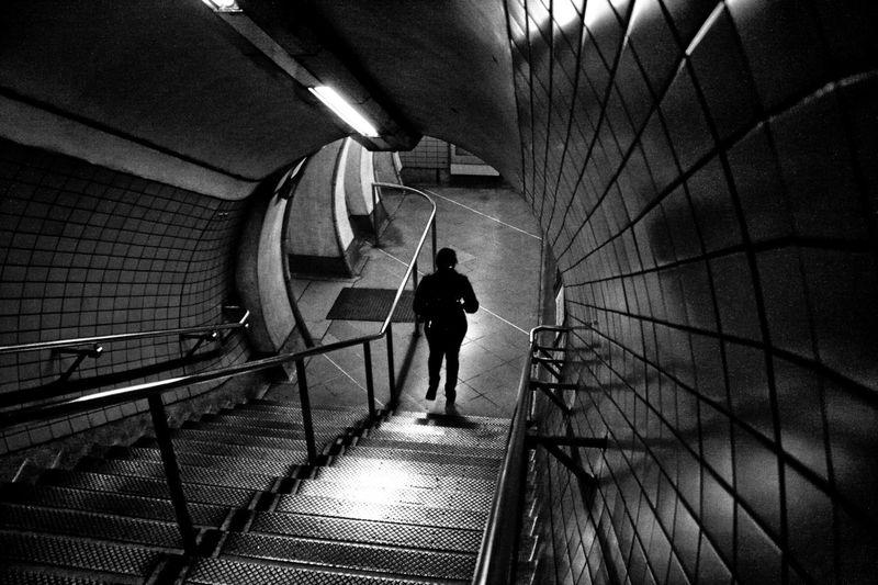 Rear view of man walking on footpath in subway