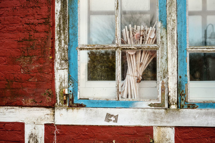 Bundle Of Stick On Closed Window Of Abandoned House