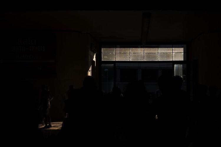 Silhouette people standing in dark room
