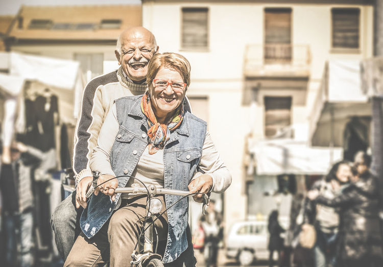 Portrait of senior couple on bicycle at street in city