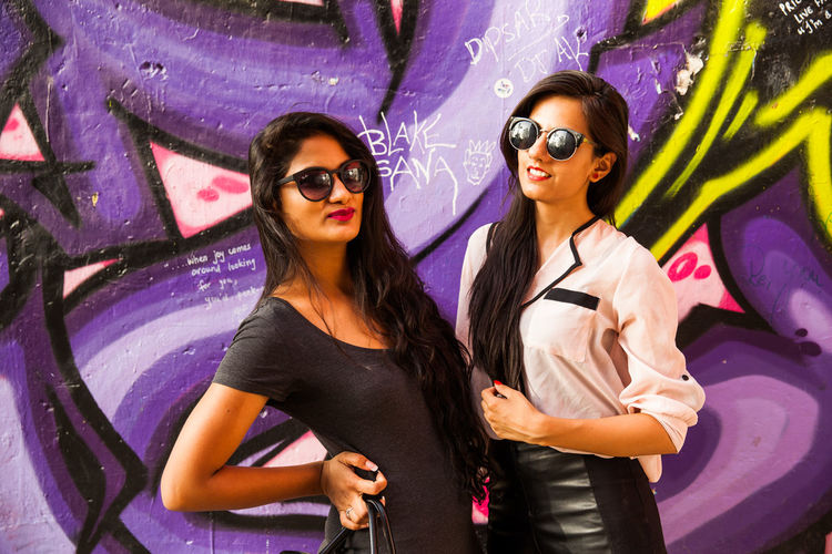 Two fashionable girls in front of graffiti art Graffiti Art Graffiti Wall Fashionable Girls Indian Girls Millenials Indian Fashion Posing For Camera Girls In Leathe