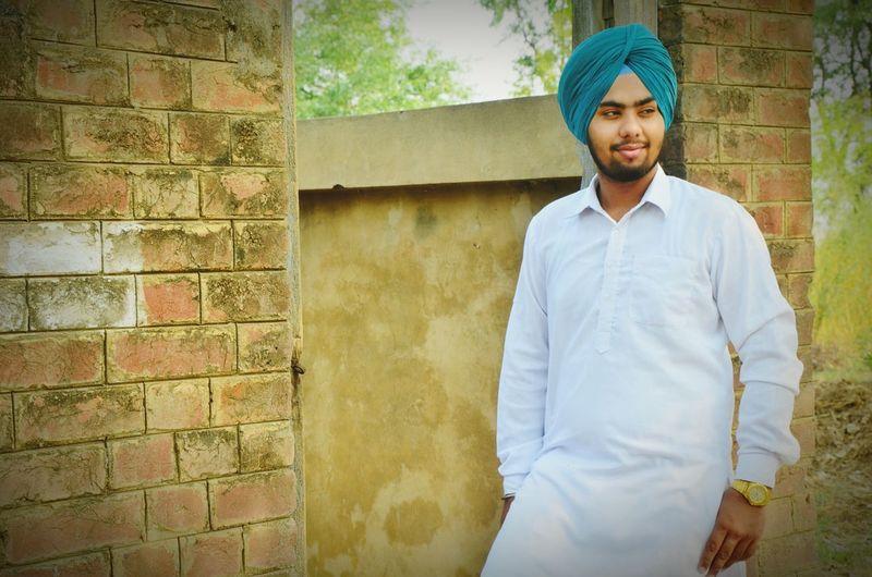 Young man wearing kurta and turban by wall