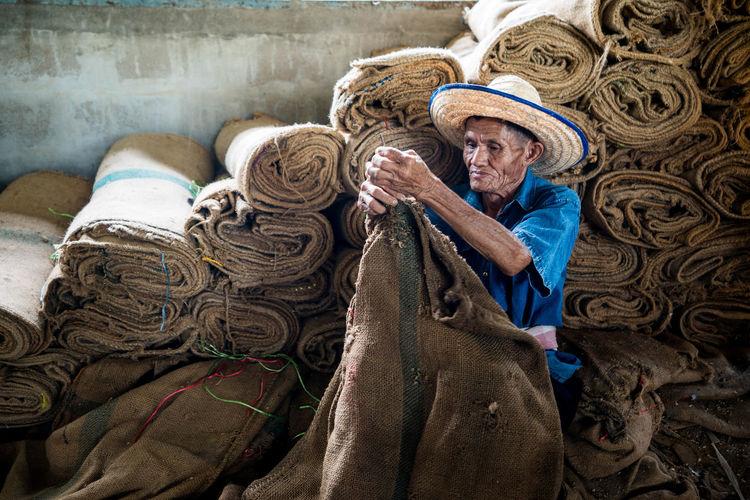 Man folding sacks in workshop