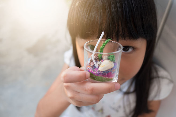 A Thai little girl showing of a glass of ocean objects she prepared for a handmade candle Asian  Candle Thai Adorable Child Childhood Children Only Close-up Day Elementary Age Focus On Foreground Freshness Girls Handmade Headshot Holding Kid Lifestyles One Person Outdoors Preparation  Real People Selective Focus