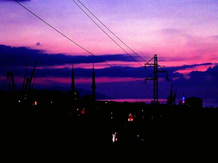 Silhouette electricity pylon against dramatic sky during sunset