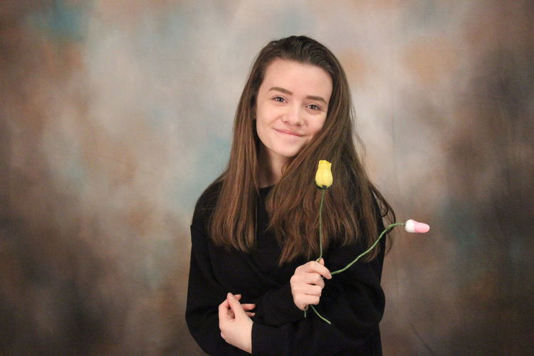 Portrait of smiling woman holding roses while standing against backdrop