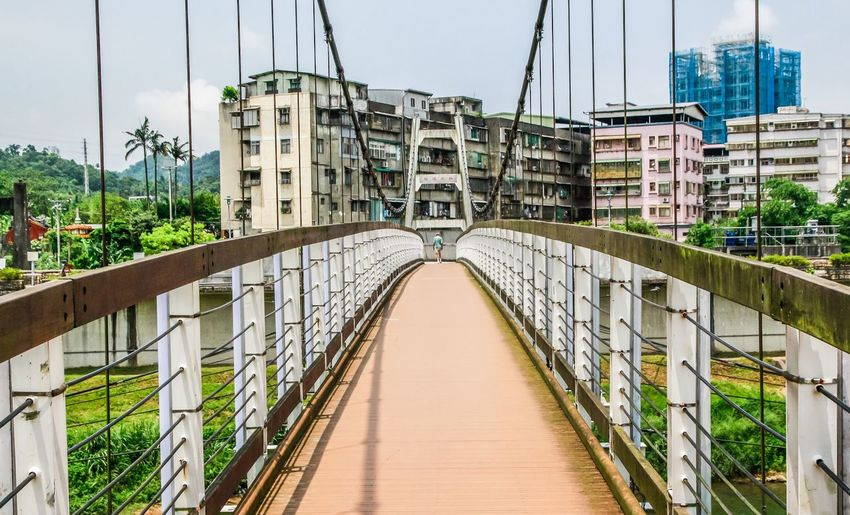 REMOTE PERSON WALKING ON A NARROW SUSPENDED BRIDGE
