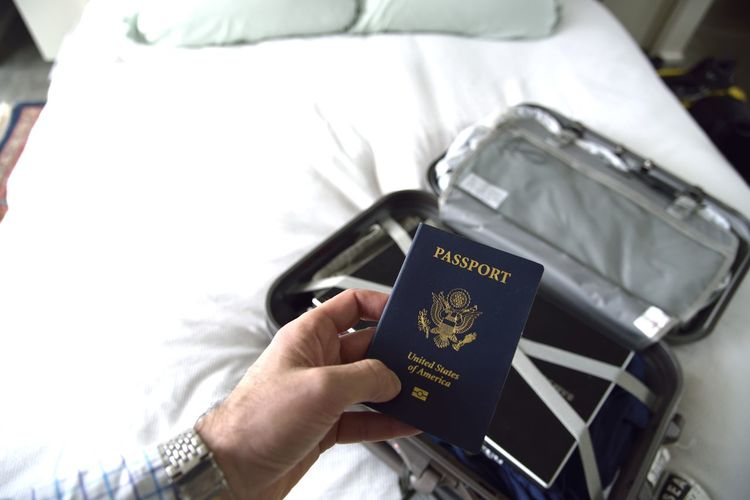 Cropped hand of man holding passport in room