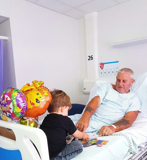 Grandfather And Grandson Playing With Toys On Bed In Hospital Ward