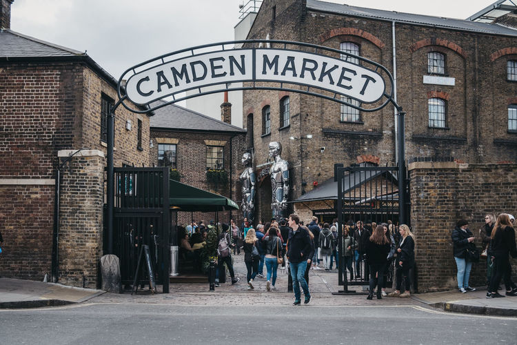 People entering Camden Market through the gates, under a name sign. Started with 16 stalls in March 1974, Camden Market is one of the busiest retail destinations in London. Brick Outdoors Lifestyles Western Script Adult Building Day Crowd Men Communication Large Group Of People Women Street Real People Text City Built Structure Group Of People Architecture Sign Building Exterior Tourists People Leisure Activity Travel Destinations Europe England Market Famous Place Weekend Activities Trabel Camden Market, London Camden Town Uk London