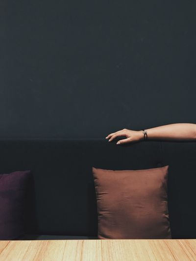 Cropped hand of woman on sofa against wall