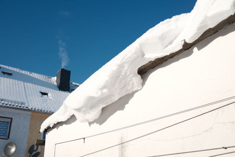 Low angle view of clothes drying on snow against buildings