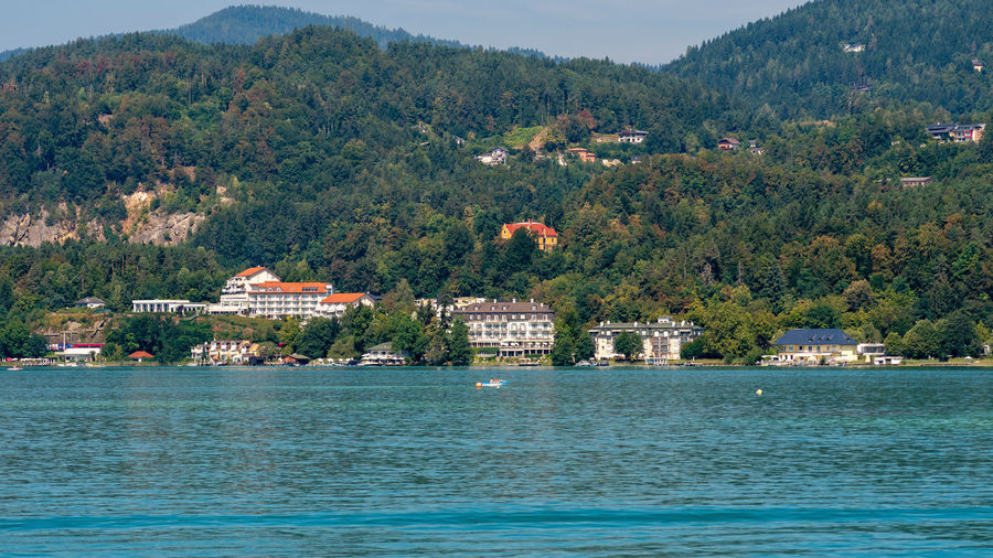 WORTHERSEE, AUSTRIA - AUGUST 08, 2018: Great scenery from the boat to the shore line of the lake, beautiful buildings, mountains, forests, highways. Tourists who enjoy a variety of water recreation types. Nature Day Outdoors Austria Carinthia Carinthian Lakes Tourist Tourists Lake Wörthersee Recreation  Leisure Landscape Water Sea Boats Motorboat Speedboats Summer People Holidays Fun Travel Beach Resort Lifestyle Sunny Rest Joy Waves Europe Alps Alpine Alpine Lake Tree Building Exterior Plant Mountain Architecture Built Structure Land Building Scenics - Nature No People Travel Destinations Beauty In Nature House Waterfront View Into Land Turquoise Colored
