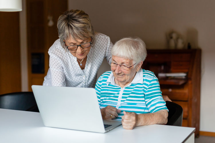 Senior Women Using Laptop At Table In Home