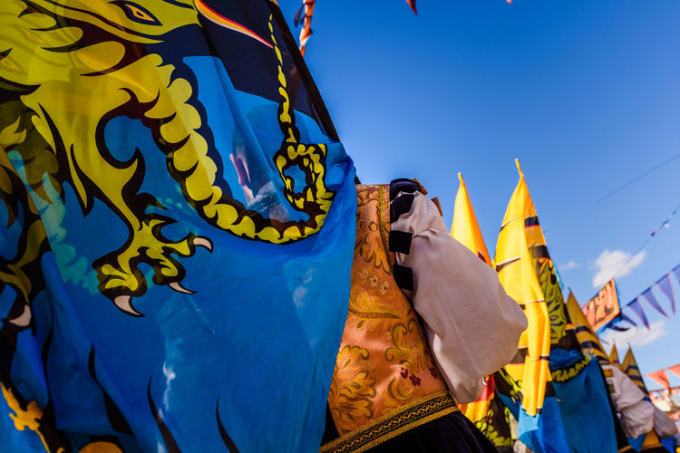 Low angle view of yellow flags against blue sky
