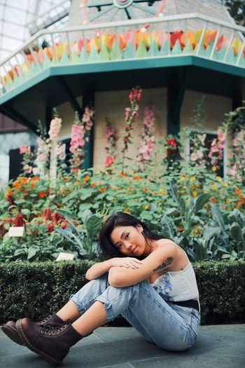 Portrait of woman sitting against plants